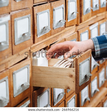 A file cabinet drawer full of files opened by hand - stock photo