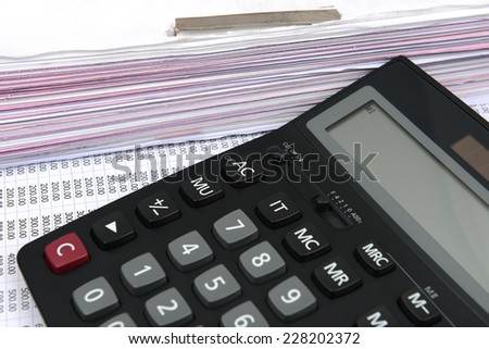 a file folder with documents and calculator on a chart number - stock photo