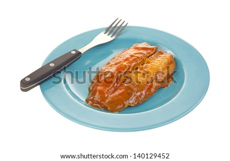 A fillet of smoked herring covered with tomato sauce on a blue plate with a fork on a white background. - stock photo
