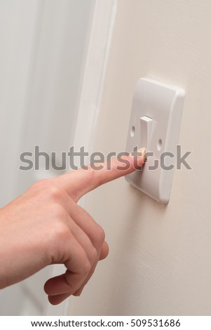A finger presses on a single white light switch on a cream wall next to a white doorway in what looks to be a domestic dwelling