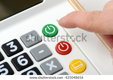 a finger pressing the on / power button on a calculator, focus on the button. - stock photo