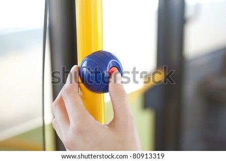 a finger pushes on a stop button at a handhold/a finger pushes on a stop button at a handhold