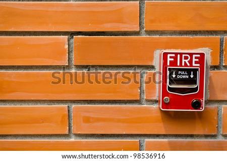 a fire alarm on brick wall - stock photo