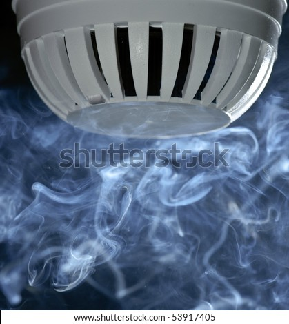 A fire detector with smoke rising. - stock photo