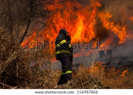 A fire fighter attending to a brush fire - stock photo