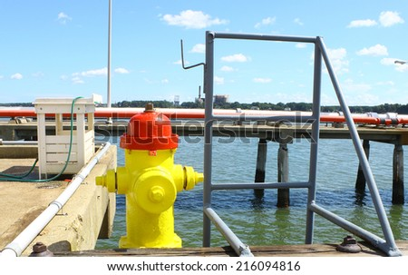 A fire hydrant,ladder and fuel lines on piers over the York river in Yorktown Virginia on a summer day - stock photo