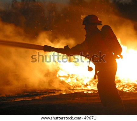 a firefighter hoses down a blaze - stock photo