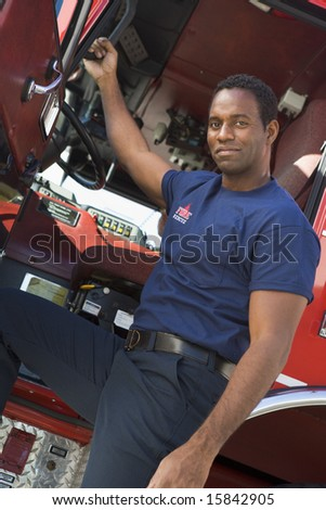 A firefighter standing by the cab of a fire engine - stock photo