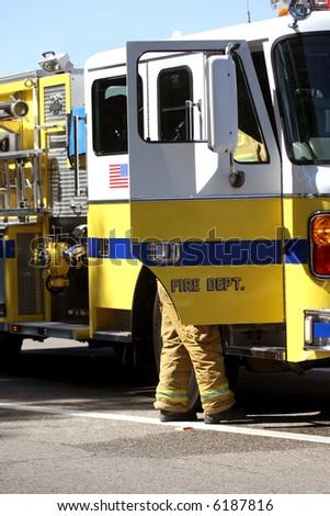 A firefighter standing next to a firetruck - stock photo