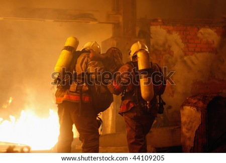 A firefighters carrying an accident victim from a fire - stock photo