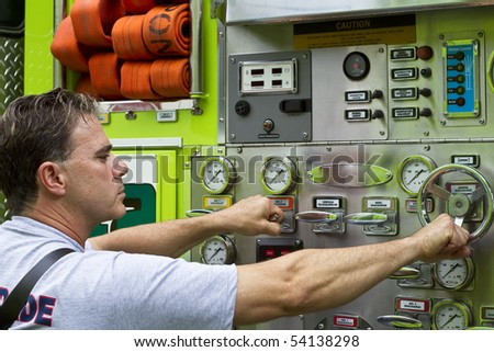 a fireman activating switches and dials on a rescue truck - stock photo