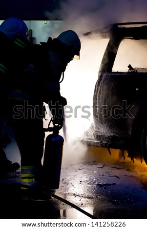 A fireman extinguishes a car-fire - stock photo