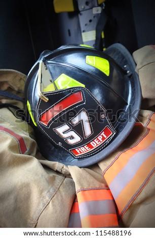 A fireman's black helmet is on a firefighters jacket uniform. - stock photo