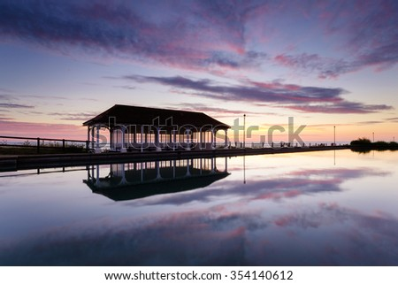 A firery sunrise over the boating lake on the promenade at Sherringham. - stock photo