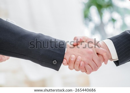 A firm handshake. Two successful businessman standing in the restaurant and drink coffee while shaking hands with each other close-up view of hands
