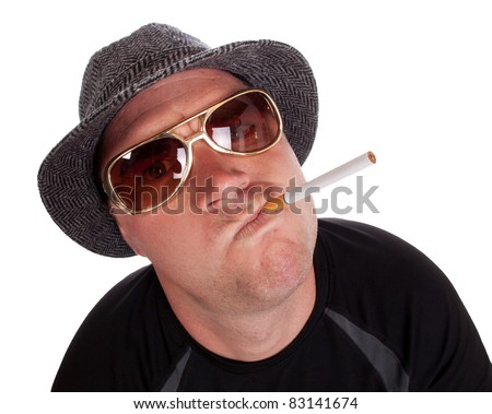 A fish eye close up of a tough guy with a cigarette in his mouth.  He is wearing sunglasses and a hat.