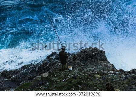 a fisherman agains big waves - stock photo
