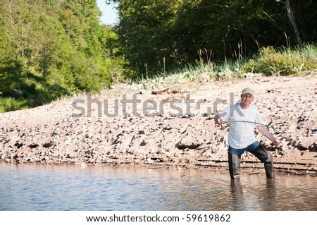 A fisherman fishing on a river - stock photo