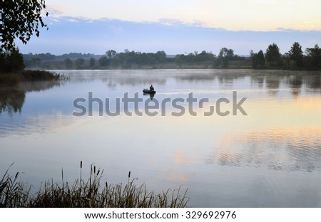 A fisherman in a boat floating on the water in the dawn sun in the fog - stock photo