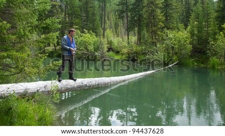 A fisherman on the shore of spininglm mountain river - stock photo
