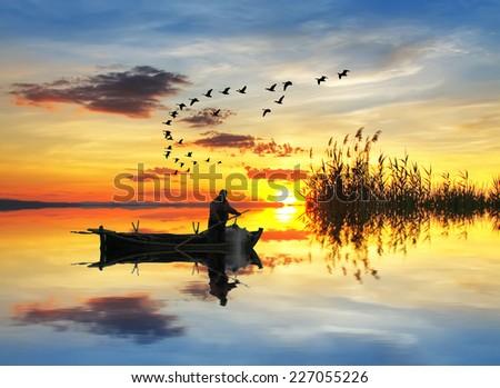 a fisherman pulling nets before sunrise - stock photo