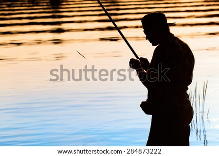 A fisherman putting on the bait - stock photo