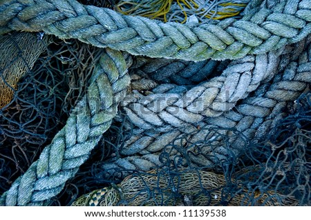 A fisherman's ropes and nets, piled on a wharf - stock photo