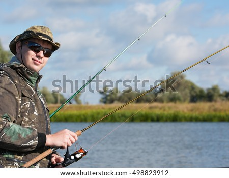 A fisherman with a spinning rod to catch fish. Sunglasses and fishing clothes. Summer landscape in the background
