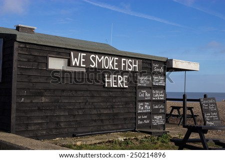 A fishermans' hut on Aldeburgh beach, with chalkboard details of fish being sold.