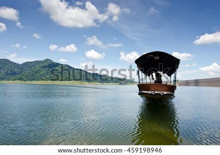 A fishing boat approaches shore area at Khun Dan dam, Nakohn Nayok Thailand - stock photo