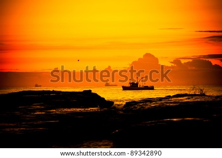 A fishing boat cruises by the shore at dawn in Wollongong, New South Wales, Australia - stock photo