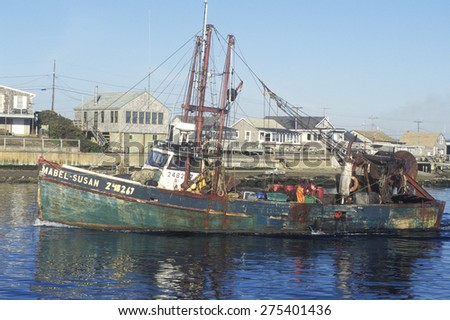 A fishing boat heading out from the wharf at Point Judith, Rhode Island - stock photo
