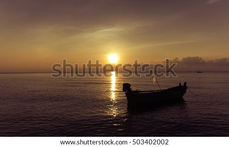 A fishing boat is floating on the sea of Thai Gulf while the sun sets in the bright sky.