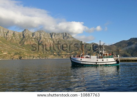 A fishing boat leaving Hout bay harbor, Cape Town in the late afternoon.