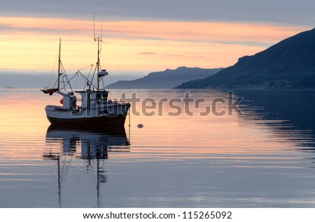 a fishing boat lies at sundown in the fjord - stock photo