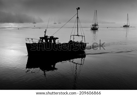 A fishing boat returns to the Cornish harbour town of Saltash in Cornwall, England. - stock photo