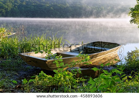 A fishing boat tied at the shore of a Pennsylvania lake with the morning sunlight shinning on the fog. - stock photo