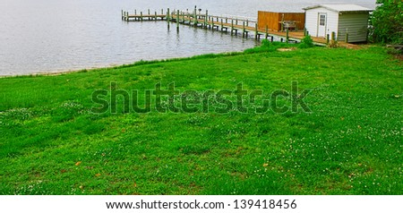 A fishing pier/boat dock with a shed and cleaning station over the Piankitank river in Middlesex county Virginia. - stock photo