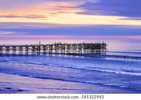 A Fishing Pier Boldly Reaching Into The Vastness Of The Pacific Ocean At Sunset Near San Diego California, USA - stock photo