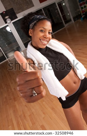 a fit girl giving thumbs up after a good workout - stock photo