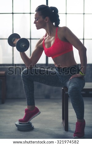 A fit, muscular woman sitting on a city loft gym bench is lifting weights, resting her elbow against her knee, curling the weights towards her as she looks down at her hand. - stock photo