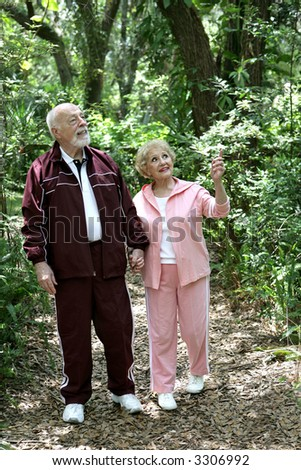 A fit retired senior couple walking together in the woods. - stock photo