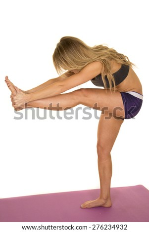 A fit woman doing a leg stretch, bending over. - stock photo