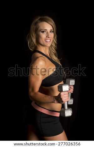 A fit woman in her fitness clothes, holding on to her weights. - stock photo