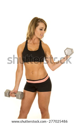 A fit woman looking down at her arm, while she is lifting weights.