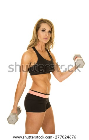 A fit woman standing with a serious expression, working out with weights.