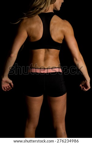 a fit woman with her back to the camera. - stock photo
