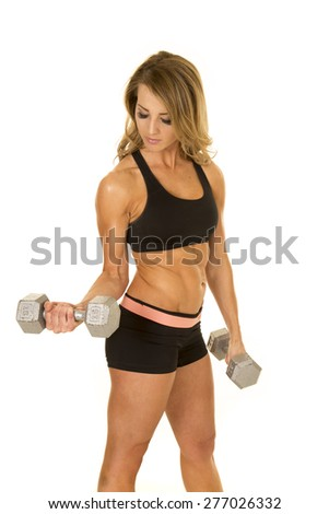 A fit woman working out her arms, with weights. - stock photo