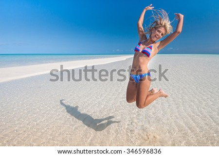 A fitness model jumping on pure white beach with rippled sand - stock photo