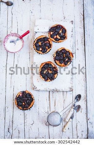 A five delicious homemade cherry and plum tartlets, pie, fruit quiche from above on a country wooden table with powder of sugar and sifter. Rustic style. - stock photo